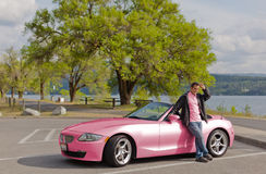 Pretty pink car and matching driver Foto de archivo