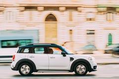 Coche blanco Mini Cooper Mini Countryman Fast del color que se mueve en la calle de la ciudad imagen de archivo libre de regalías