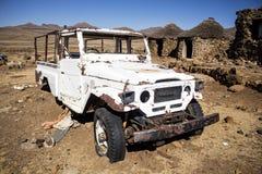 Coche blanco roto primer en pueblo abandonado Imágenes de archivo libres de regalías