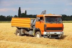 Coche camión en el campo de trigo, cosechando Imagenes de archivo