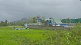 Coche cerca de la casa dañada por el huracán de Damrey debajo del cielo cubierto