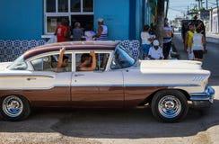 Coche clásico americano blanco rojo en Santa Clara Cuba con la opinión de la vida en las calles imagenes de archivo