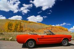 Coche clásico de los convertiblesports en el camino pavimentado Colorado Rocky Mountains de la carretera en otoño Imagenes de archivo