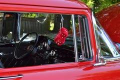 Coche clásico rojo con el tablero de instrumentos negro y dados rojos Imagen de archivo libre de regalías