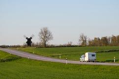 Coche con la caravana en un paisaje verde Imagen de archivo libre de regalías