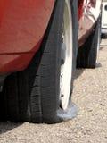 Coche con los neumáticos planos Foto de archivo