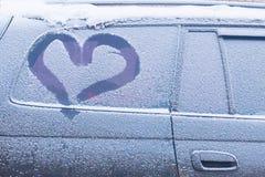 Coche con ventanas congeladas y un corazón dibujado sobre el vidrio foto de archivo