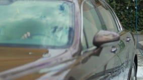 Coche costoso que deja la ranura después del carwash, coche de lujo siguiente que toma su lugar metrajes