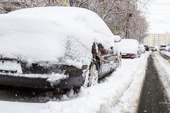 Coche cubierto con nieve en el estacionamiento después de una tormenta Imágenes de archivo libres de regalías