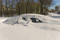Coche cubierto con nieve en nieve acumulada por la ventisca de la ventisca del invierno Imagen de archivo libre de regalías