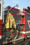 Coche de bomberos, capa y casco Imagen de archivo libre de regalías