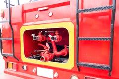 Coche de bomberos y manguera de bomberos roja del primer, fuego y rescate imagenes de archivo