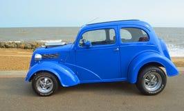 Coche de carreras azul clásico en la 'promenade' de la orilla del mar fotografía de archivo
