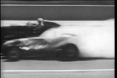 Coche de carreras que conduce a través de la pared del fuego a la meta, Indy 500 almacen de video