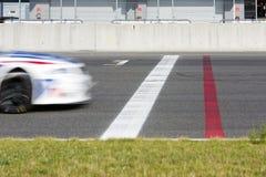 Coche de carreras que cruza la meta Imagen de archivo libre de regalías
