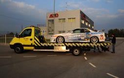 Coche de competición que es transportado en un camión en puesta del sol Fotografía de archivo libre de regalías