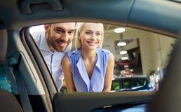 Coche de compra de los pares felices en salón del automóvil o salón Fotografía de archivo libre de regalías