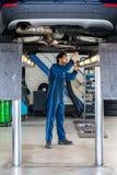 Coche de Examining Under The del mecánico en el garaje Fotografía de archivo libre de regalías