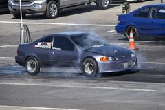 Coche de Honda en la línea de salida que hace una quemadura Imagen de archivo libre de regalías