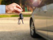 Coche de la falta de definición en la llave del coche de la tenencia del fondo y de la persona en manos imagenes de archivo