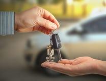 Coche de la falta de definición en la llave del coche de la tenencia del fondo y de la persona en manos fotos de archivo libres de regalías