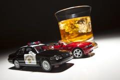 Coche de la policía y de deportes al lado de la bebida alcohólica Fotografía de archivo libre de regalías
