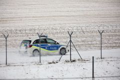 Coche de la seguridad que comprueba la pista en invierno imagen de archivo