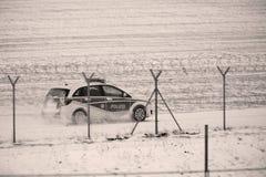 Coche de la seguridad que comprueba la pista en invierno imagenes de archivo