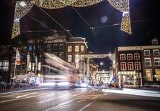 Coche de las linternas que pasa abajo de la calle en la noche Foto de archivo
