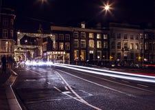 Coche de las linternas que pasa abajo de la calle en la noche Amsterdam Imagen de archivo