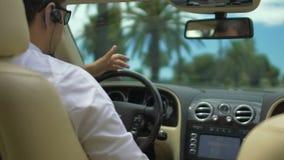 Coche de lujo de conducción masculino, teniendo conversación sobre las auriculares, hombre de negocios ocupado almacen de video