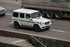 Coche de lujo Mercedes Benz blanca G que apresura en la carretera vacía fotografía de archivo