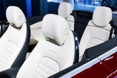 Coche de lujo moderno dentro Interior del coche moderno del prestigio Asientos de cuero cómodos Carlinga de cuero perforada blanc imagen de archivo libre de regalías