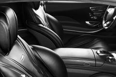 Coche de lujo moderno dentro Interior del coche moderno del prestigio Asientos de cuero cómodos Carlinga de cuero perforada Volan foto de archivo libre de regalías