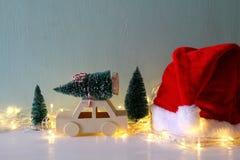 Coche de madera que lleva un sombrero siguiente de Papá Noel del árbol de navidad Imágenes de archivo libres de regalías