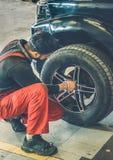 Coche de mantenimiento del hombre y apertura del neumático del coche imagen de archivo