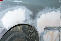 Coche de plata con la pintura dañada y cuerpo abollado del metal del accidente del desplome con la carrocería inacabada sobre alu Imágenes de archivo libres de regalías