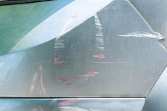 Coche de plata con la pintura rasguñada con las líneas rojas del otro vehículo dañado en el accidente o el estacionamiento, cierr Imágenes de archivo libres de regalías