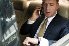 Coche de Talking Using Phone del hombre de negocios dentro Imágenes de archivo libres de regalías