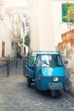 Coche de tres ruedas viejo parqueado en la calle estrecha Imagen de archivo