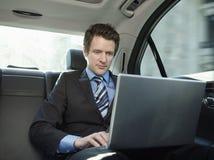 Coche de Using Laptop In del hombre de negocios Imagen de archivo libre de regalías