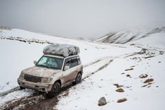 Coche de viajeros en paisaje del camino de la nieve de la montaña coche en un paso de montaña, pico del jeep 4x4 del soporte Aven imágenes de archivo libres de regalías