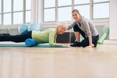 Coche del gimnasio que ayuda a la mujer mayor en su entrenamiento Foto de archivo