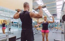 Coche del hombre que entrena a la mujer con pesas de gimnasia Foto de archivo