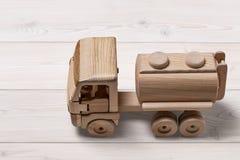 Coche del juguete con la cisterna en fondo de madera Foto de archivo