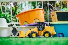 Coche del juguete de Tracktor con las cajas de juguetes en el jardín fotografía de archivo