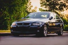 Coche del negro de BMW en la puesta del sol imagen de archivo