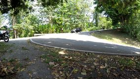Coche del vehículo que se mueve abajo en el camino escarpado y curvado de la cumbre almacen de metraje de vídeo