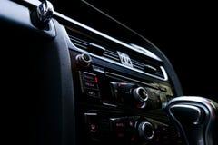 Coche deportivo de lujo moderno dentro Interior del coche del prestigio Cuero negro Detalle del coche dashboard Medios, clima y n foto de archivo libre de regalías