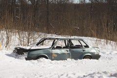 Coche destruido abandonado en la nieve Esqueleto del tra innecesario Fotos de archivo libres de regalías